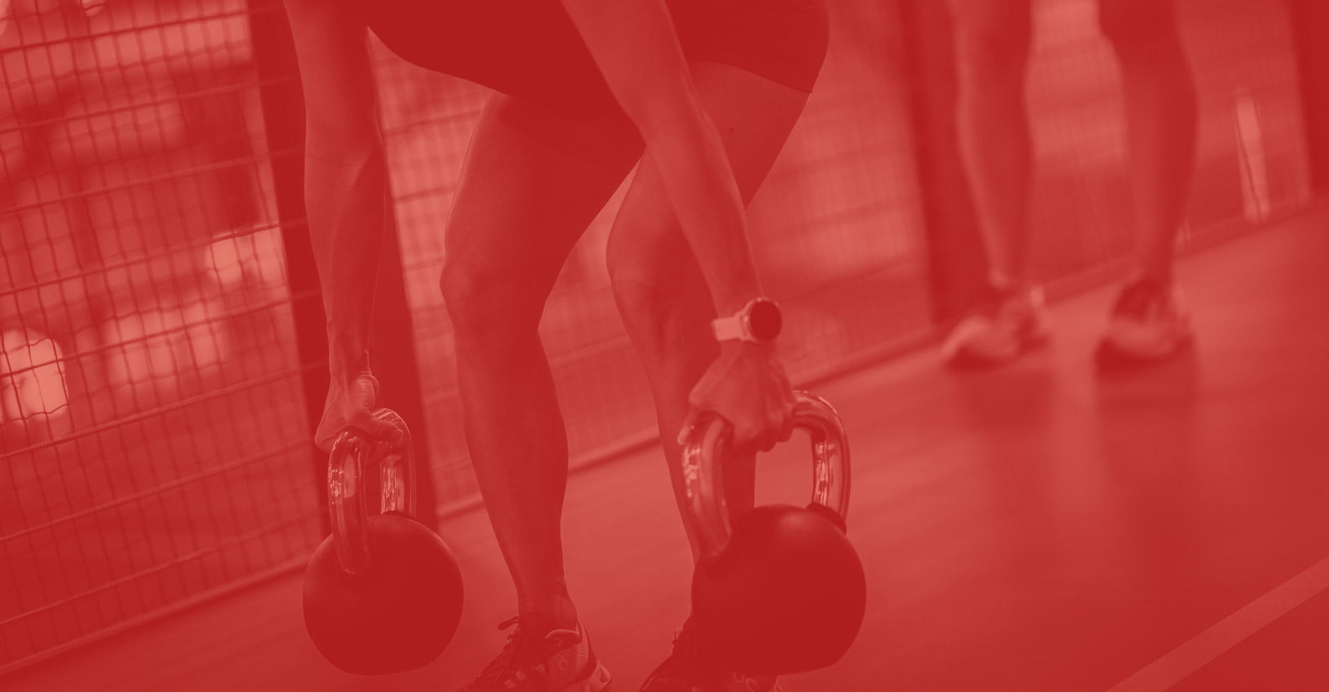 Woman lifting kettle bells on an indoor track